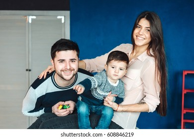 young family having fun at home on a background of a wall