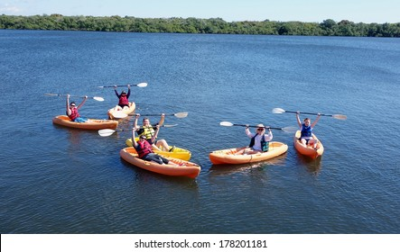 Young family having fun kayaking with teenagers in South Florida