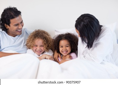 Young family having fun on the bedroom