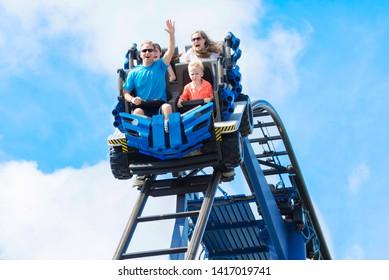 Junge Familie, die Spaß beim Reiten einer Achterbahn in einem Themenpark hat. Schrei, lachen und einen lustigen Sommerurlaub zusammen genießen.