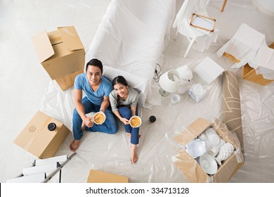 Young family having lunch after unpacking in new flat