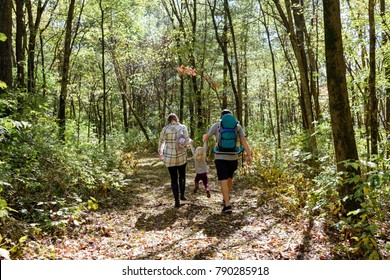 Young family hiking in the woods in autumn