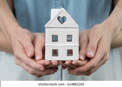 Young family is holding house in hands