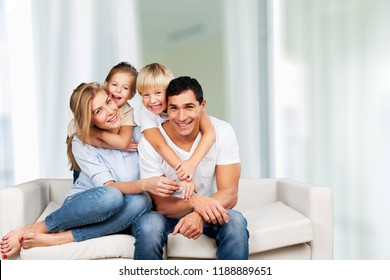 Young family at home smiling at camera