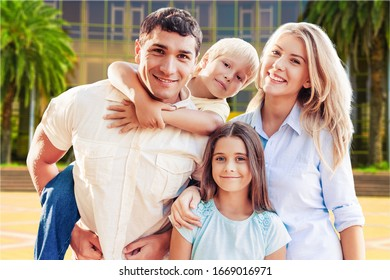 Young family at home smiling at the camera