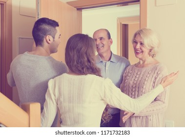 young family inviting elderly parents to come inside