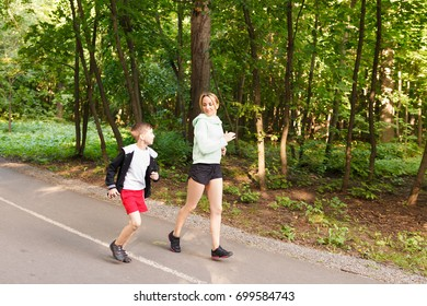 Young family jogging in the open air Happy mom with 9 years old child running at summer park