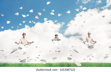 Young family keeping eyes closed and looking concentrated while meditating on clouds among flying paper planes with bright and beautiful landscape on background.