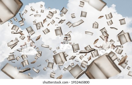 Young family keeping eyes closed and looking concentrated while meditating among flying books in the air with cloudy skyscape on background.