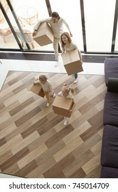Young family with kids entering new home carrying boxes, children helping parents to relocate into big modern house with terrace on moving in day concept, mortgage and relocation, vertical top view