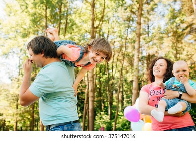 Young family with kids having fun with pillows and colored balloons outdoors. Parents with two children relax in a sunny summer garden. Mother, father, little girl and baby boy playing in park.