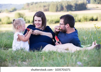 Young family with kids having picnic outdoors. Parents with child relax in a sunny summer garden.