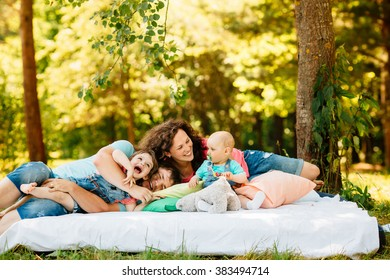 Young family with kids having picnic with colored pillows outdoors. Parents with two children relax in a sunny summer garden. Mother, father, little girl and baby boy playing in park.