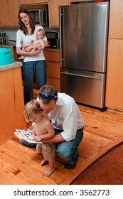 Young Family in kitchen. Mom holding Baby and Dad reading to young son.