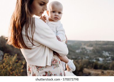 Young family with little daughter walking along the mountain slopes on the high yellow grass. Mom carries her daughter in the hands of the sunset. mother's love and warmth