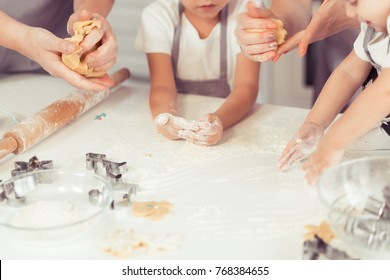 Young family with little kid and baby sons making gingerbread cookies at home.