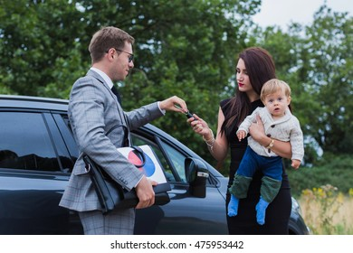 young family makes car purchase. A young boy at the hands of her mother. Happy baby reaches for the keys