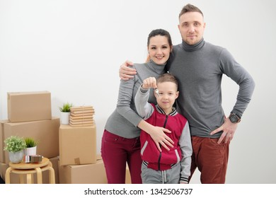 Young family, man woman and child son in new apartments. The child holds the keys to the apartment. Boxes with cargo on a white background. The concept of moving to a new home.