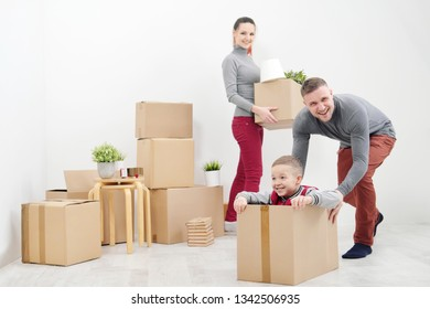 Young family, man woman and child son in new apartments. Boxes with cargo on a white background. The concept of moving to a new home.