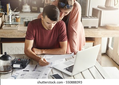 Young family managing budget, reviewing their bank accounts using generic laptop pc and calculator in kitchen. Husband and wife doing paperwork together, paying taxes online on notebook computer