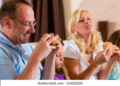 Young family - mother, father and daughters - is eating hamburger or fast food at home