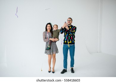 Young family of mother father and son celebrating with confetti over white background