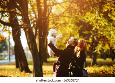 young family and newborn son posing for the camera in autumn park