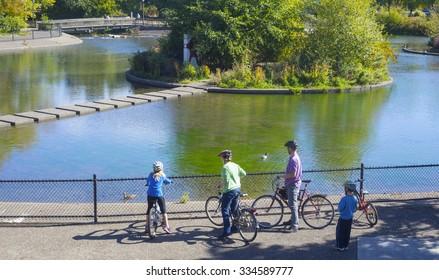 A young family observe ducks at Alton Baker Park in Eugene Oregon.