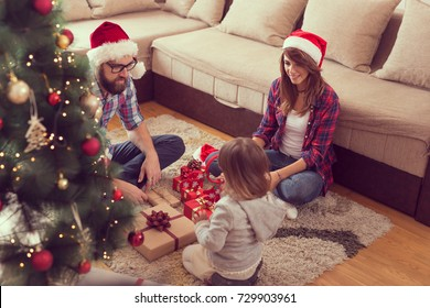 Young family on Christmas morning exchanging presents and enjoying their time together. Focus on the parents