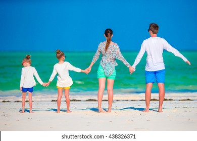 Young family on vacation. Happy father, mother and their active kids having fun on their summer beach holidays