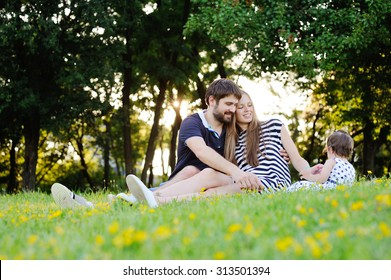 Young family on vacation in the park. mother, father and little daughter sit on the grass. Dad gives his daughter a small flower.