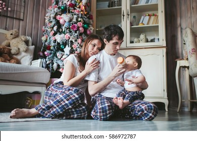 young family in pajamas to bottle feed the little boy