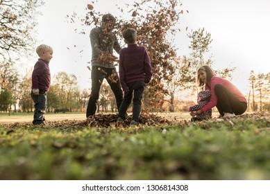 Young family of parents and three kids having fun in an autumn park throwing leaves in the air enjoying their time together.