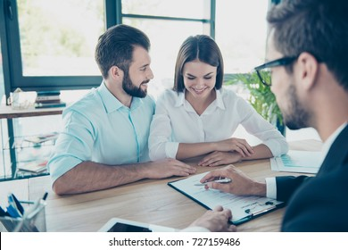 Young family, partners are making a deal with dealer about purchase. Lawyer is showing where to sign the contract, couple are happy and smiling, all are well dressed, in nice modern light work station
