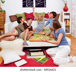 a young family is playing board-games in their bed