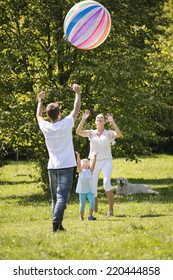 Young family playing with huge inflated ball in garden