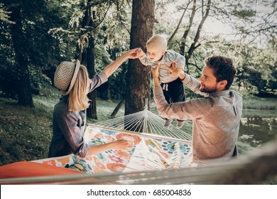 Young family playing with son on a hammock in park on camping trip, hipster mother smiling at baby boy near handsome father holding him, sunny morning background