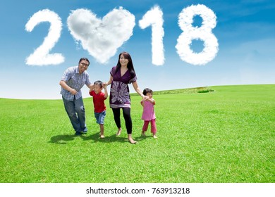 Young family playing together while running in the park with clouds shaped heart and numbers 2018 in the sky