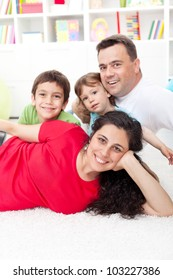 Young family portrait in their home - focus on the woman