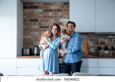 Young family, pregnant woman and her partner or husband with dog and cat at kitchen