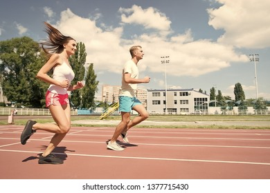 Young family promoting healthy lifestyle. Woman and man run stadium. Coach and sportsman motion run training before race. Couple runners training outdoors. Couple or family live healthy lifestyle.