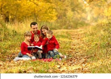 young family reading the Bible in autumn forest