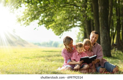 a Young family reading the Bible in nature