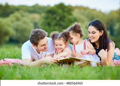 Young family reading a book outdoors lying on the grass in the park.
