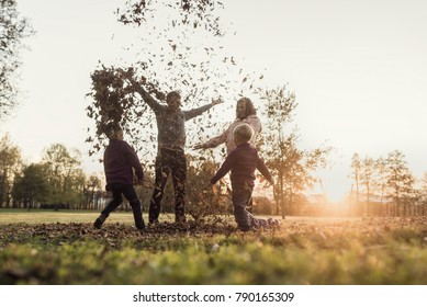 Young family rejoicing in an autumn sunset standing throwing leaves in the air in a rural field backlit by the orange glow of the sun, toned retro effect.