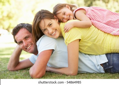 Young Family Relaxing In Park
