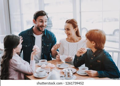 Young Family is Resting in Cafe. Family is Mother, Father, Daughter and Son. People is Eating Cakes and Drinking Tea. Persons is Sitting at Table. People is Happy and Smiling. Sunny Daytime.