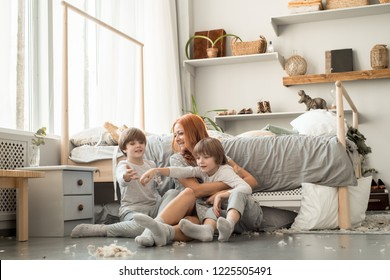 Young family resting together in parent's bed.After the pillow fight, a lot of feathers. Happy boys. Concept of maternal love, parenthood, happy family