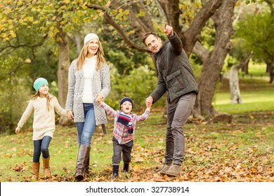 Young family running in leaves on an autumns day