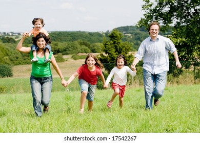 Young family running over a farmer´s field